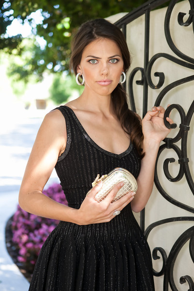Kristin wears an Azzedine Alaia black/silver dress, Stephen Silver Fine Jewelry diamond and white gold inside out hoops and diamond and white gold vortex cocktail ring, and holds a DVF beige clutch with gold embellishment.